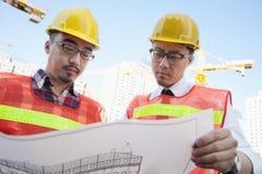Twee architecten die een blauwdruk in openlucht bij een bouwwerf bekijken stock afbeeldingen