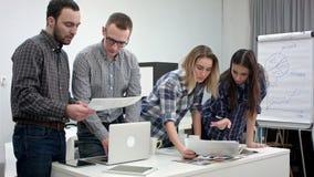 Twee architecten die lay-out bespreken terwijl vrouwelijke medewerkers die kleurenpalet bekijken stock videobeelden