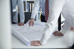 Twee architecten die over een blauwdruk in het bureau, medio sectie bespreken stock afbeeldingen