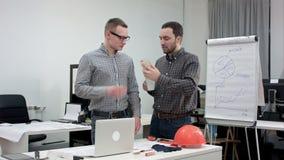 Twee architecten die telefoongesprek hebben tijdens koffiepauze stock video