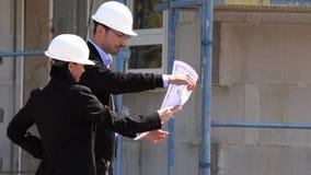 Twee architecten een man en een vrouw in bouw in witte helmen stock videobeelden