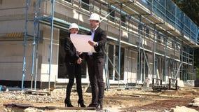 Twee architecten een man en een vrouw in bouw in witte helmen stock footage