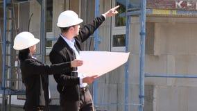 Twee architecten een man en een vrouw in bouw in witte helmen stock video
