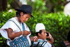 Twee Arhuaco-mensen kleedden zich met hun traditionele kleren gebruikend hun cellphones in Cartagena DE Indias stock foto