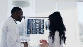 Twee artsen bekijken röntgenstralen Medisch De belangrijkste Amerikaanse man van artsenafro en Kaukasische vrouw die bekijken rön stock video