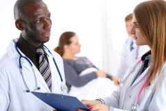 Twee artsen delen en bespreken belangrijk document op klembordpa royalty-vrije stock foto's