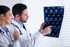 Twee artsen die een aftasten samen analyseren stock afbeeldingen
