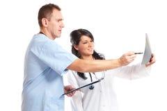 Twee artsen die geduldige röntgenstraal bekijken stock foto