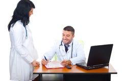 Twee artsen die gesprek in bureau hebben Stock Foto's