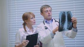 Twee artsen die patiëntenröntgenstralen in het ziekenhuis onderzoeken stock video