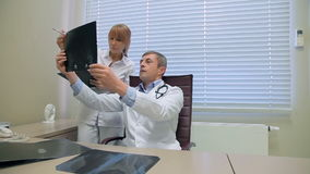 Twee artsen die patiëntenröntgenstralen onderzoeken stock footage