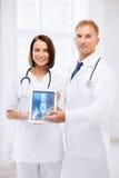 Twee artsen die röntgenstraal op tabletpc tonen Stock Foto's