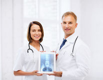 Twee artsen die röntgenstraal op tabletpc tonen Stock Foto