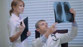 Twee artsen met x-ray drukken stock footage