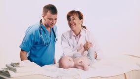 Twee artsen onderzoeken een babyjongen stock video