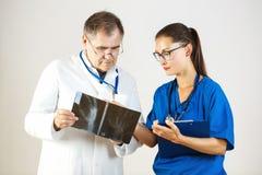 Twee artsen onderzoeken een Röntgenstraal en bespreken het probleem stock foto's