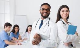Twee Artsen in Witte Lagen die aan Camera op Conferentie stellen stock fotografie