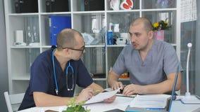 Twee artsenmensen komen in het bureau van het hoofd van de therapieafdeling samen stock video
