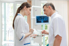 Twee artsentandartsen die panoramische foto van tanden op monitor kijken Stock Afbeeldingen