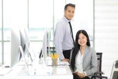 Twee Asain zakenman en onderneemster die samen binnen weg ontspannen stock afbeeldingen