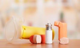 Twee astmainhaleertoestel, aerochamber en medicijn op abstract roze Stock Afbeelding