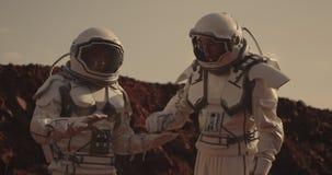 Twee astronauten die steekproef op Mars onderzoeken stock footage