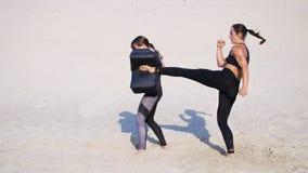 Twee atletische, jonge vrouwen in zwarte geschiktheidskostuums zijn bezig geweest met een paar, werken schoppen uit, leiden, voer stock videobeelden