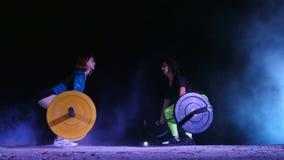 Twee atletische meisjes, atleten, die oefeningen met barbell doen Bij nacht, in het licht van zoeklichten, een stobascope, binnen stock videobeelden