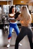 Twee atletische meisjes gekleed in een sportkleding doen samen achterhurkzit met zware geschiktheidsbal in de moderne gymnastiek royalty-vrije stock afbeeldingen