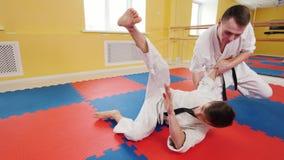 Twee atletische mensen die hun aikidovaardigheden in de studio opleiden Een mens grijpt zijn tegenstander en werpt hem op de vloe stock foto's