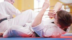 Twee atletische mensen die hun aikidovaardigheden in de studio opleiden Het werpen van de tegenstander op de vloer stock afbeeldingen
