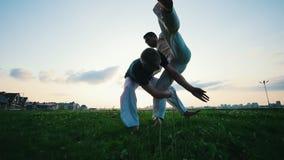 Twee atletische mensen die op gras, één vechten van hen klopten andere, de zomer, zonsondergang stock videobeelden
