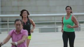 Twee atletische vrouwen in sportkleding die in publiek lopen Gezonde actieve levensstijl stock video