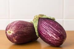 Twee aubergines op een lijst Stock Fotografie