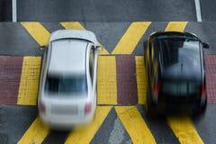 Twee auto's kruisen de voetgangersoversteekplaats, hoogste mening stock afbeeldingen