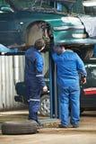 Twee autowerktuigkundige die autoopschorting diagnostiseert Stock Foto