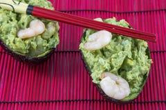 Twee avocadosalade met garnalen en eetstokjes op de rode mat stock afbeeldingen