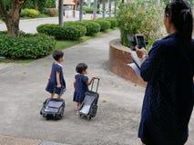Twee Aziatische babymeisjes die hun nieuwe karretjeschooltassen trekken terwijl wordt gefotografeerd door haar moeder stock fotografie