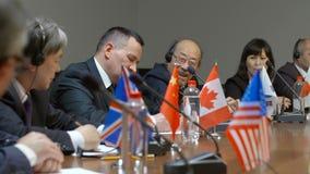 Twee Aziatische deelnemers van internationale economische vriendschappelijke top bespreken een vraag bij rondetafel Diverse polit stock video