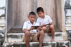 Twee Aziatische jongens die schooluniformen dragen spelen spel maar zij royalty-vrije stock foto's