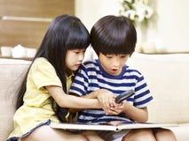 Twee Aziatische kinderen die met meer magnifier spelen royalty-vrije stock foto