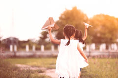 Twee Aziatische kindmeisjes die en stuk speelgoed document vliegtuig in werking stellen spelen Royalty-vrije Stock Afbeeldingen