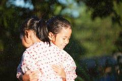 Twee Aziatische kindmeisjes die regenjas dragen die elkaar in de regenachtige dag koesteren royalty-vrije stock foto's