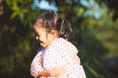 Twee Aziatische kindmeisjes die regenjas dragen die elkaar in de regenachtige dag koesteren royalty-vrije stock afbeeldingen