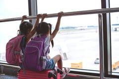 Twee Aziatische kindmeisjes met rugzak die vliegtuig bekijken en op samen het inschepen in de luchthaven wachten stock foto's
