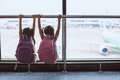 Twee Aziatische kindmeisjes met rugzak die vliegtuig bekijken en op samen het inschepen in de luchthaven wachten royalty-vrije stock foto