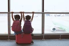 Twee Aziatische kindmeisjes met rugzak die vliegtuig bekijken en op samen het inschepen in de luchthaven wachten royalty-vrije stock afbeelding