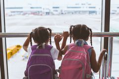 Twee Aziatische kindmeisjes met rugzak die vliegtuig bekijken en op samen het inschepen in de luchthaven wachten royalty-vrije stock fotografie