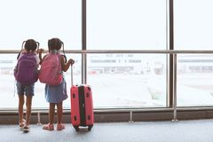 Twee Aziatische kindmeisjes met rugzak die vliegtuig bekijken en op samen het inschepen in de luchthaven wachten royalty-vrije stock foto's