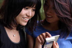 Twee Aziatische meisjes die een cellphone bekijken stock foto's